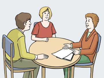Drei Leute sitzen zusammen am Tisch und besprechen etwas