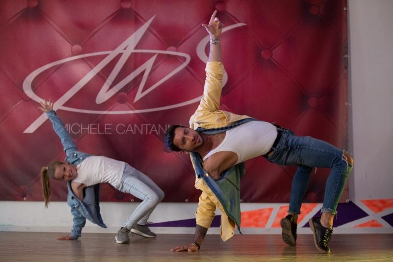 Ein Mädchen und ein Erwachsener in Tanzbewegung: Beide stehen nebeneinander auf den Zehenspitzen nach hinten gebeugt. Mit einer Hand stützen sie sich auf dem Boden ab, der andere Arm zeigt nach oben.