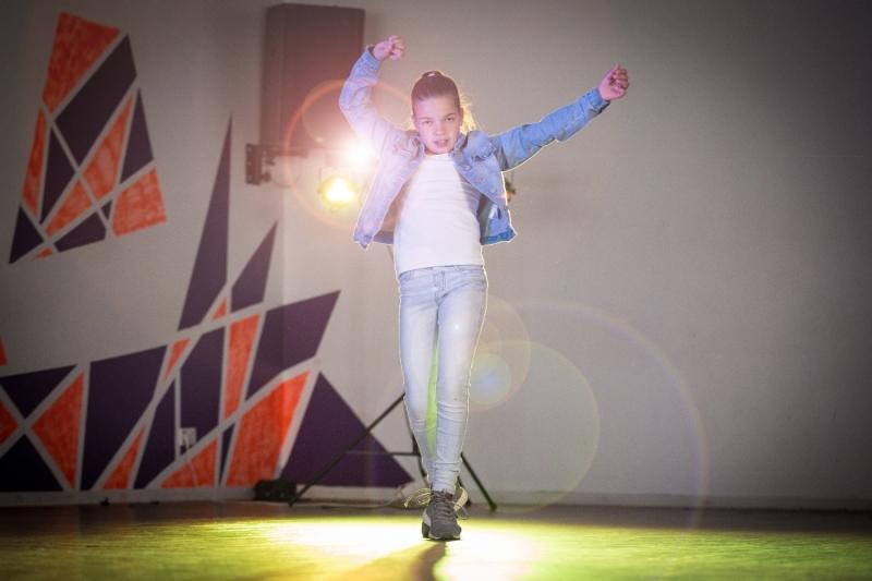 Ein zehnjähriges Mädchen in Turnschuhen, Jeans, weißem Shirt und Jeansjacke tanzt vor einem Scheinwerfer. Sie springt hoch und wirft ihre Arme in die Luft.