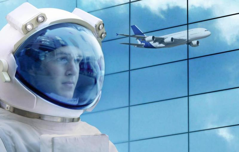 Man with space helmet and reflection of an airplane in a glass wall.