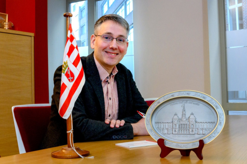 Bremeninvest project manager Manuel Kühn with the Bremen flag and a plate showing Ho Chi Minh City's town hall.